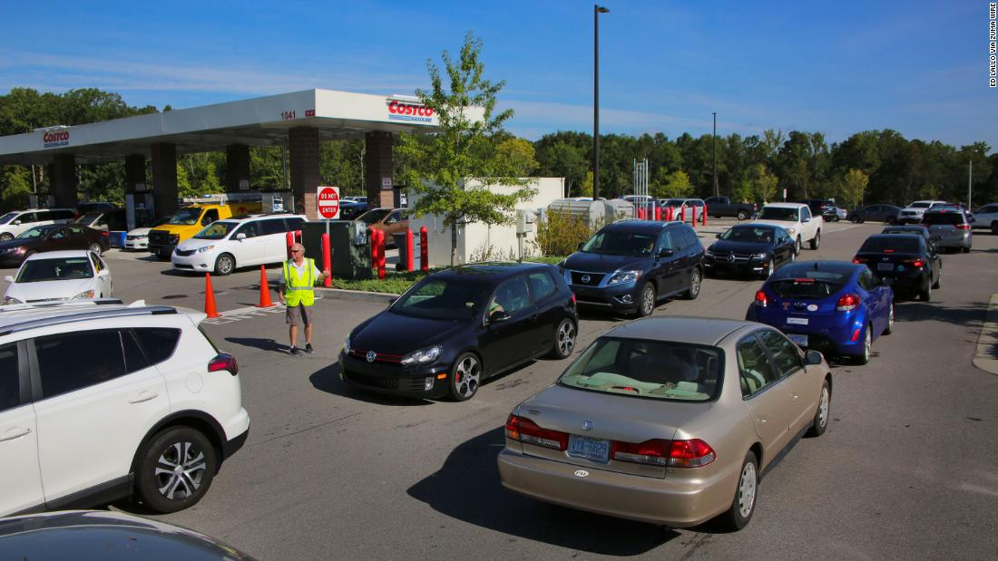 A Costco employee attempts to direct traffic at gas pumps in Apex, North Carolina, near Raleigh on September 11.
