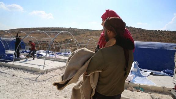 Layla's uncle carries her to her family's newly pitched tent -- she has been unable to walk since birth.