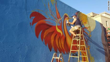 Local artist and project coordinator Dani Sánchez works on the carpet mural featuring a phoenix motif.