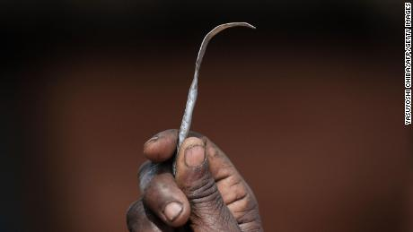 A former female genital mutilation (FGM) cutter shows a homemade tool from a nail used for FGM.