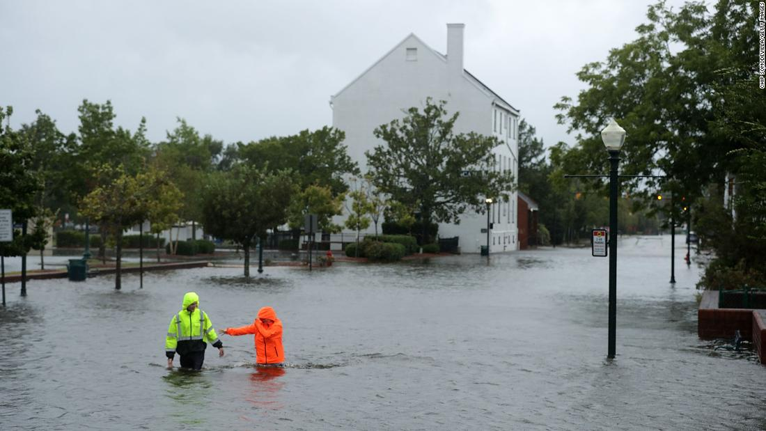 Residents wade through streets flooded by the Neuse River in New Bern on September 13.