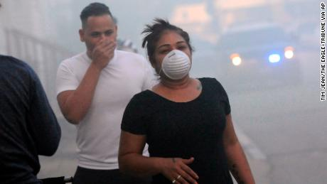 Residents protect their faces against the smoke while being evacuated Thursday in Lawrence, Massachusetts.