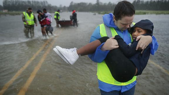 Volunteers help rescue three children from a flooded home in James City, North Carolina, on Friday, September 14.