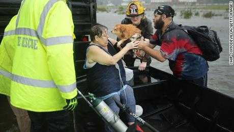 Rescue workers from Township No. 7 Fire Department and volunteers from the Civilian Crisis Response Team help rescue a woman and her dog from their flooded home in James City, North Carolina during Hurricane Florence.