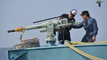 Crew of a whaling ship check a whaling gun or harpoon before departure at Ayukawa port in Ishinomaki City on April 26, 2014. A Japanese whaling fleet left port on April 26 under tight security in the first hunt since the UN's top court last month ordered Tokyo to stop killing whales in the Antarctic.    AFP PHOTO / KAZUHIRO NOGI (Photo by KAZUHIRO NOGI / AFP)        (Photo credit should read KAZUHIRO NOGI/AFP/Getty Images)