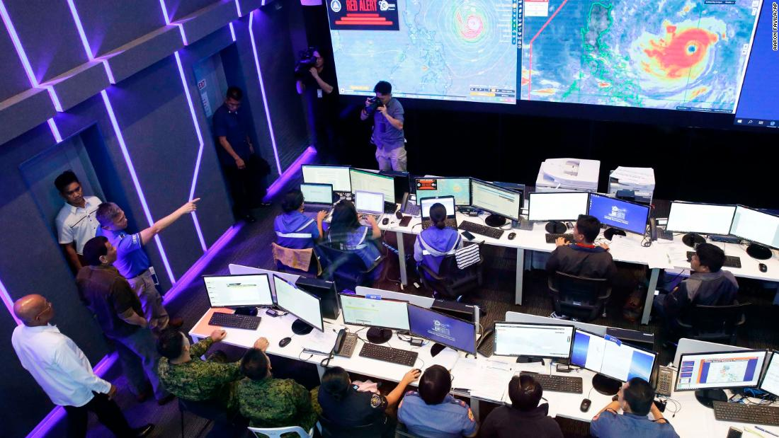 Duterte, second from left, observes the disaster agency's operation center in action in Manila on September 13.