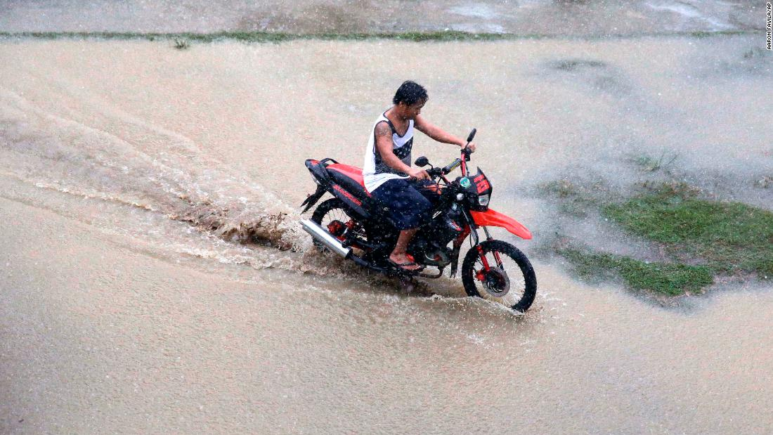 A motorcyclist maneuvers through a flooded area as rains from Super Typhoon Mangkhut begin to affect Tuguegarao City, Philippines, on Friday, September 14.
