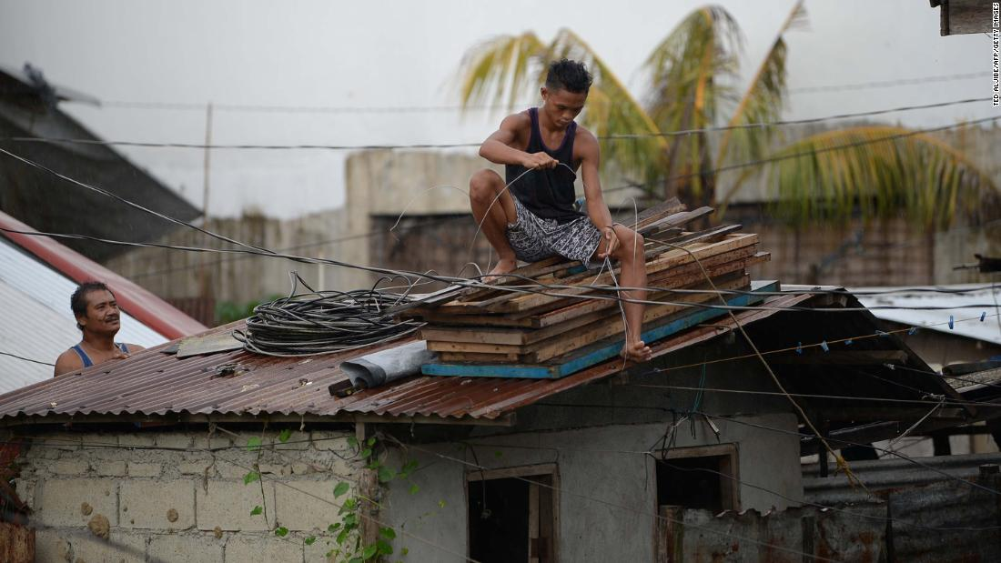 People secure the roof of a house in Tuguegarao on September 14.