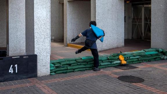 A worker steps over sandbags ahead of the typhoon