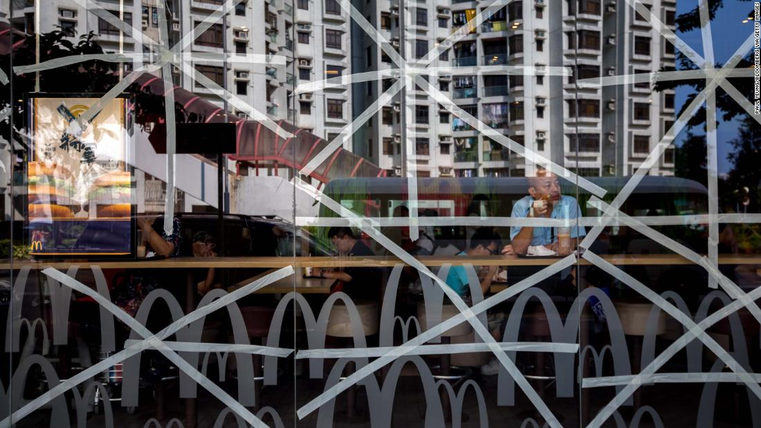 Residential buildings in Hong Kong are reflected in a McDonald's restaurant window, taped in preparation for Super Typhoon Mangkhut, on September 14. Hong Kong and Macau are currently in the typhoon's path.