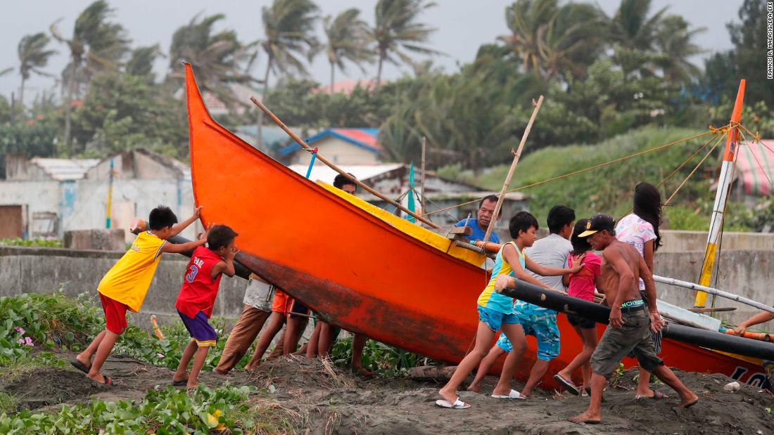 Filipino fishermen secure a boat in the town of Aparri in Cagayan province on September 14.