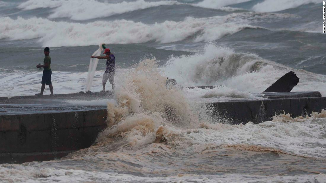 Fishermen work amid the rough seas near Aparri on September 14.