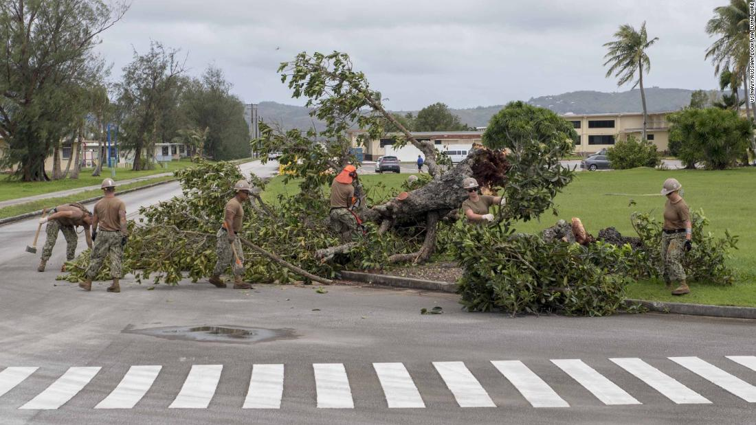 "Sailors remove debris on a US naval base in Guam on Tuesday, September 11, after the <a href=""http://www.cnn.com/2018/09/12/asia/super-typhoon-mangkhut-ompong-wxc-intl/index.html"">typhoon swept through the island territory</a>, causing flooding and power outages."
