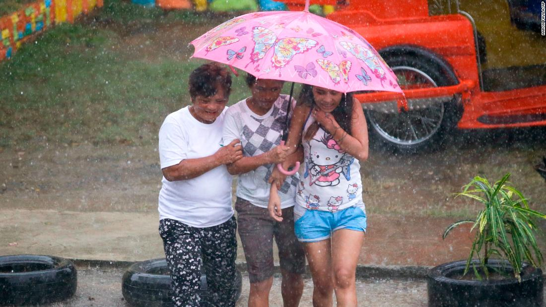 Residents make their way through heavy rains in Tuguegarao City on September 14.