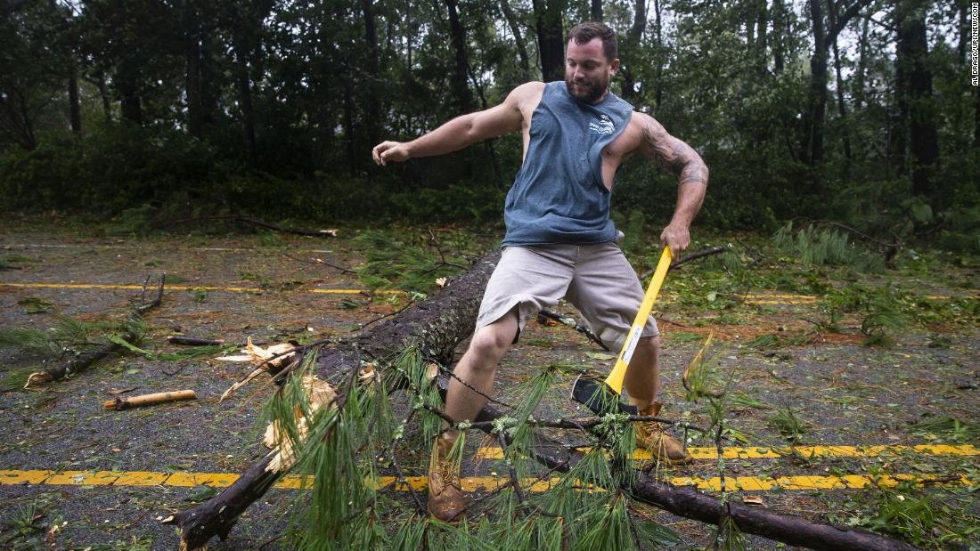 Christian Philips uses an axe to split a tree that was blocking a road in Wilmington on September 14.
