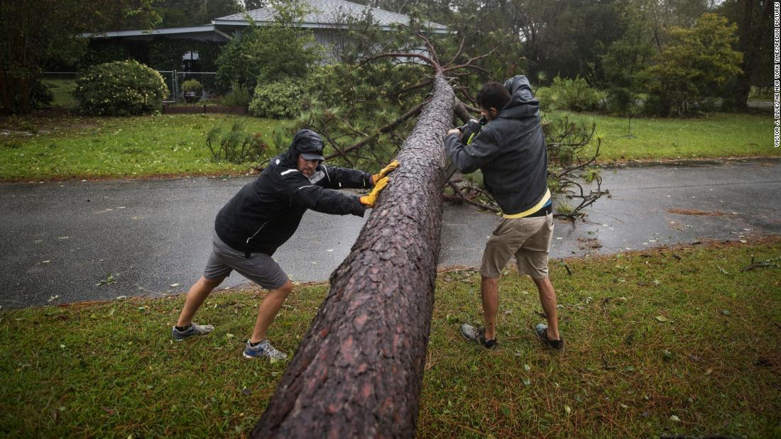 Lee Casteen, left, and Try Hinton use a chainsaw to clear a tree blocking a road in Wilmington on September 14.