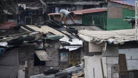 Residents reinforce the roof of their house by putting heavy tires at a slum area in Manila.