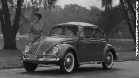 circa 1961: Promotional image of a woman standing next to a 1962 Volkswagen Beetle Sedan