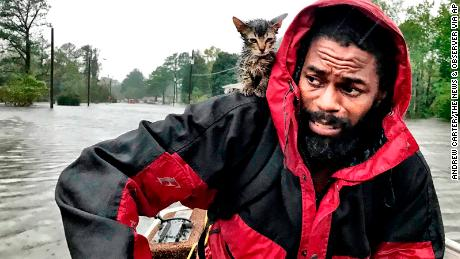 Robert Simmons Jr. and his kitten, Survivor, are rescued from floodwaters in New Bern.