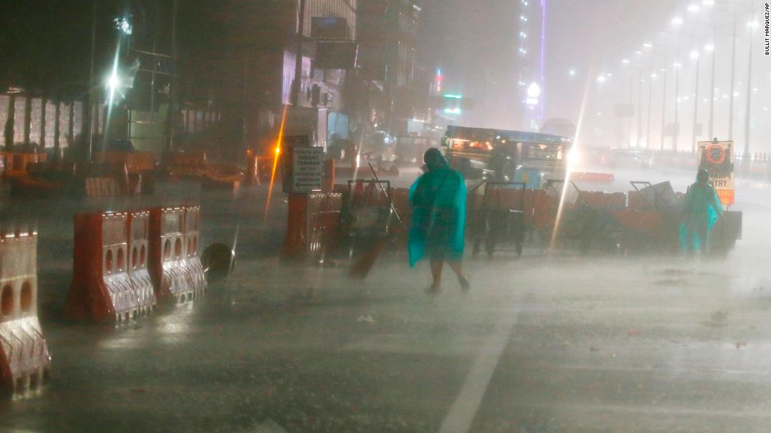Street sweepers go about their daily business as rain and strong winds pound Manila on September 15.