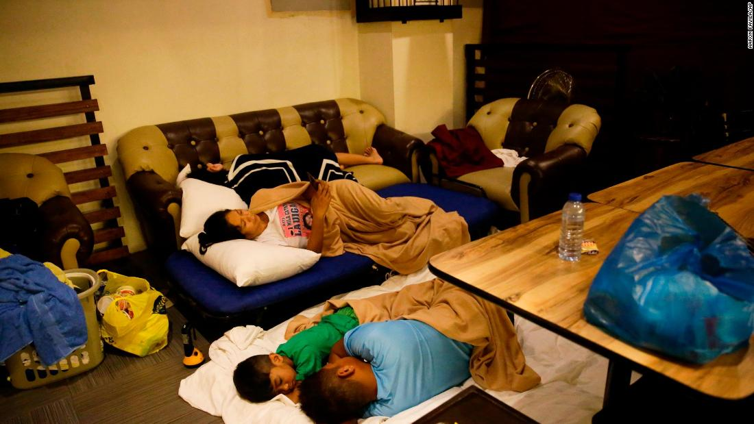 Guests sleep inside a hotel restaurant after the roof of their room was  damaged by strong winds in Tuguegarao City, Cagayan province, northeastern Philippines on September 15.