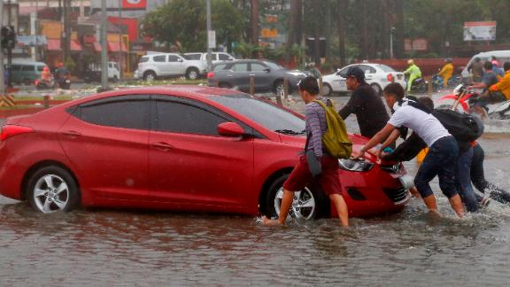 Commuters push a car through floodwaters in Manila on September 15.