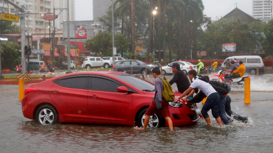 Commuters push a car through flood waters in Manila, Philippines, on September 15.