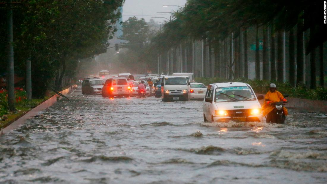 Motorists negotiate a flooded street following heavy rains and strong winds from Typhoon Mangkhut on Saturday, September 15, in Manila, Philippines.