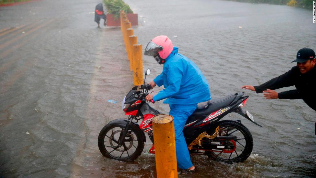 A motorist tries to avoid a flooded Manila street at the onslaught of Typhoon Mangkhut which barreled into northeastern Philippines Saturday, September 15, 2018 in Manila, Philippines.