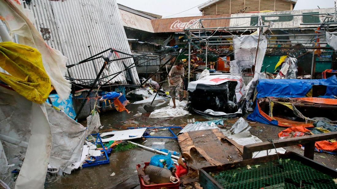 Residents walk along destroyed stalls at a public market due to strong winds as Typhoon Mangkhut barreled across Tuguegrao city in Cagayan province, northeastern Philippines on Saturday, September 15, 2018.