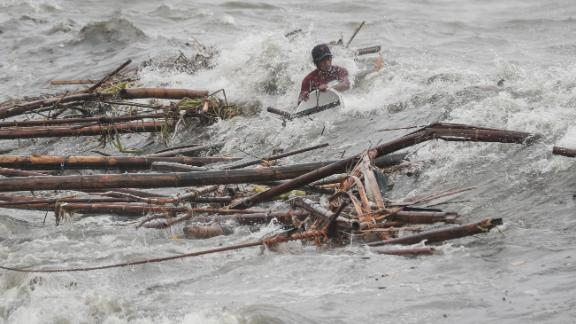 A wave overwhelms a man as he tries to recover salvageable materials in Manila, Philippines, on Saturday, September 15.
