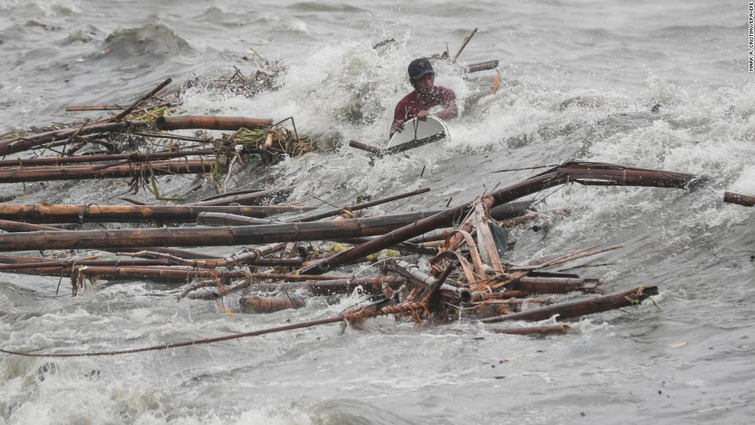 A man is hit by a wave while attempting to recover salvageable materials in Manila Bay, Manila, Philippines, Saturday, September 15, 2018.