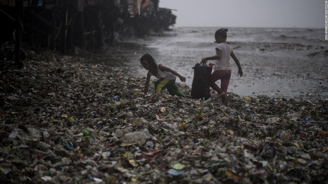 Children collect recyclable materials washed ashore by strong waves caused by Super Typhoon Mangkhut in Manila on Saturday, September 15, 2018.