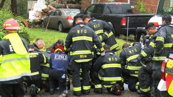 Firefighters pray at the home where a woman and her child were killed by a falling tree on Friday.