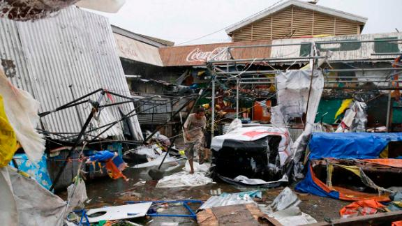 Residents walk along destroyed stalls at a public market due to strong winds as Typhoon Mangkhut barreled across Tuguegrao city in Cagayan province, northeastern Philippines on Saturday, Sept. 15, 2018. The typhoon slammed into the Philippines northeastern coast early Saturday, it
