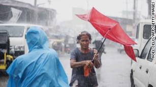 A woman in the Phillipines holds her umbrella during heavy rains caused by Typhoon Mangkhut