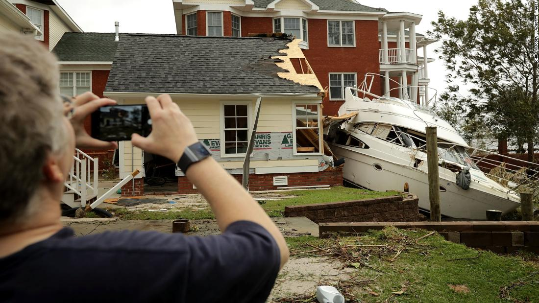 A neighbor takes photos of a boat smashed against a car garage near the Neuse River in New Bern on September 15.