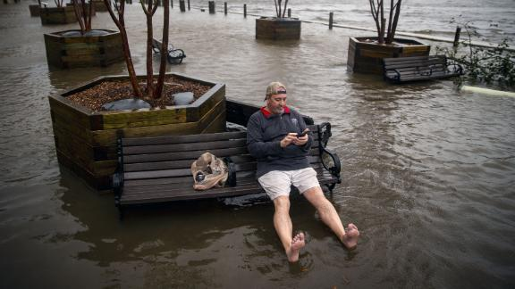 Ray Baca of Wilmington, North Carolina, checks his phone as he sits on a bench.