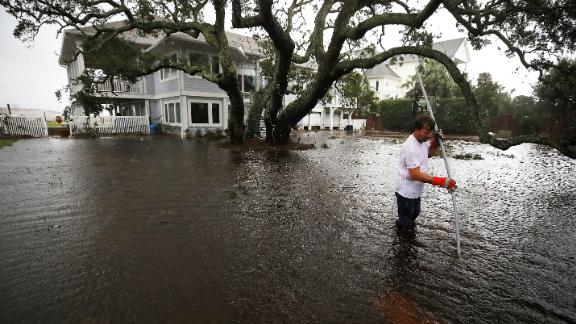 Mike Pollack searches for a drain in the yard of his flooded waterfront home in Wilmington, North Carolina, on Saturday.