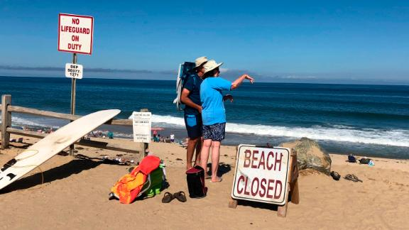 Two people look out at the shore after a reported shark attack at Newcomb Hollow Beach in Wellfleet, Mass,  on Saturday, Sept. 15, 2018.   A man boogie boarding off the Cape Cod beach was attacked by a shark on Saturday and died later at a hospital, becoming the state's first shark attack fatality in more than 80 years.  (AP Photo/Susan Haigh)
