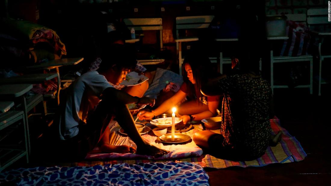 A family shares a meal by flashlight inside a temporary evacuation center after electricity was shut off following the onslaught of Typhoon Mangkhut in the city of Tuguegarao, Philippines, on Saturday.