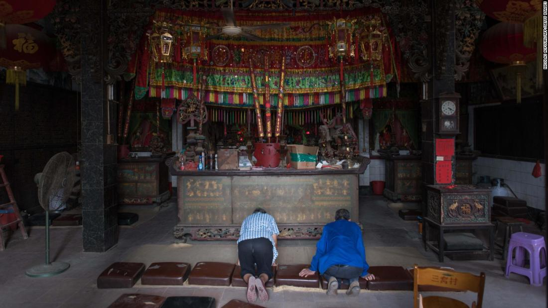 People pray inside of a temple ahead of the arrival of Typhoon Mangkhut in Sanhe village, China, on Saturday.