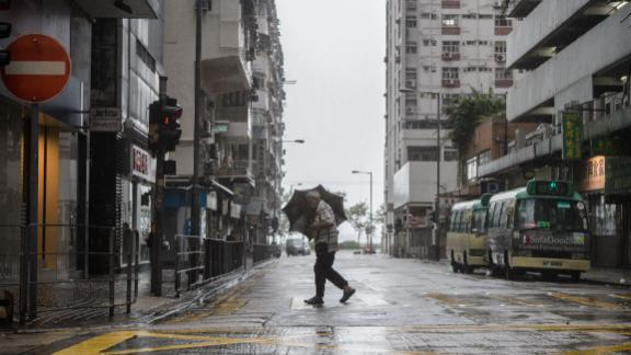 A man uses his umbrella while crossing a road as super Typhoon Mangkhut edges closer to Hong Kong on September 16, 2018.