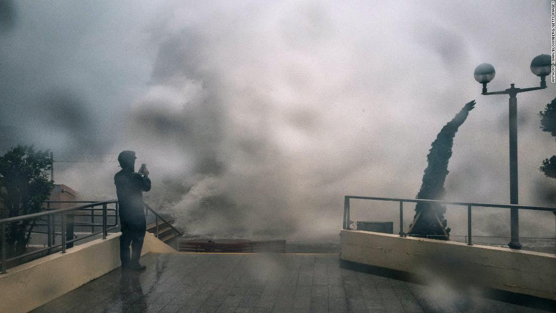 A man takes a photograph as waves crash over a promenade in Hong Kong, on Sunday.