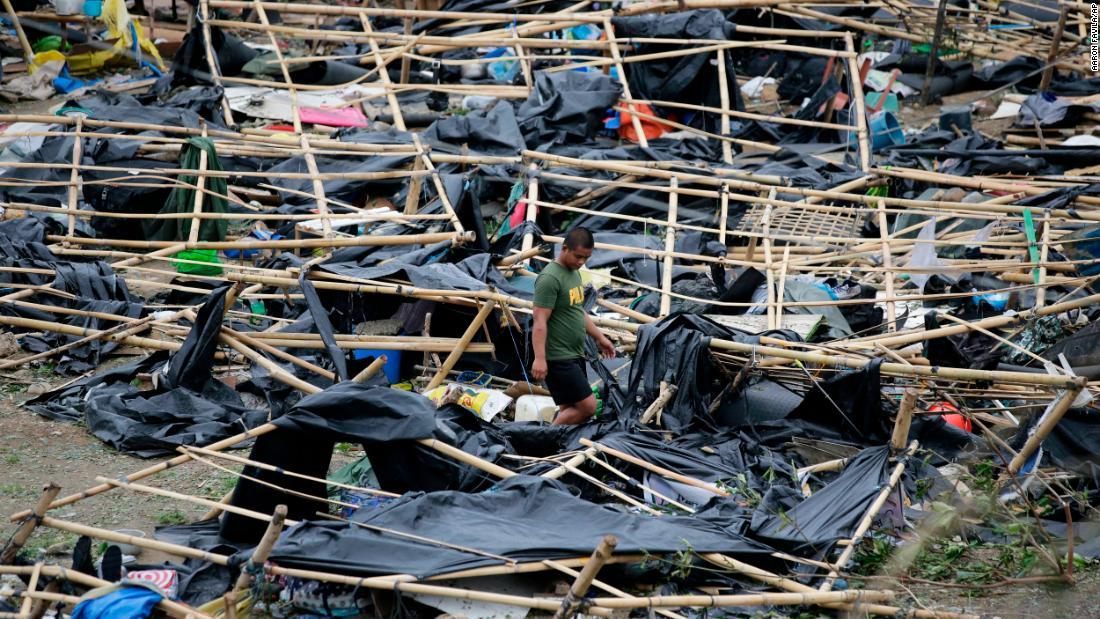 A policeman walks through makeshift tent shelters damaged by strong winds in Tuguegarao.