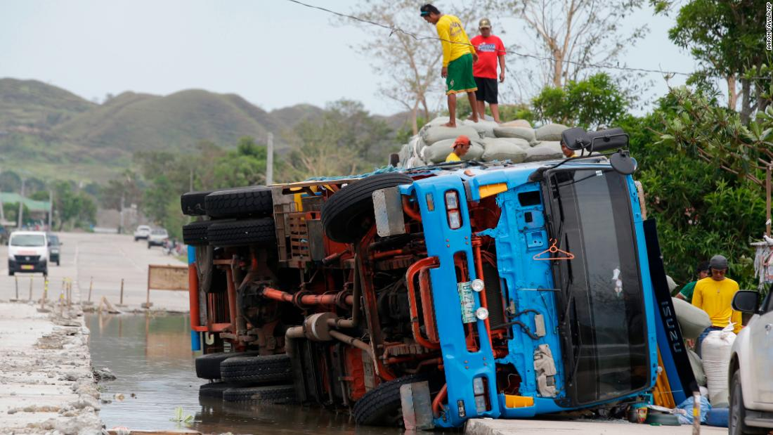 Workers transfer sacks of grains from a toppled truck in northeastern Philippines on Sunday, September 16.