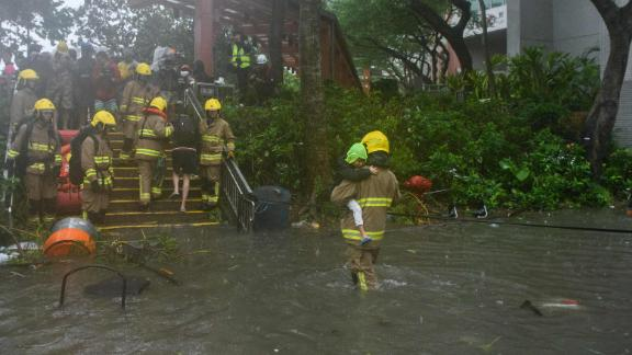 A fire rescue worker helps a child cross a flooded street in the village of Lei Yu Mun in Hong Kong.