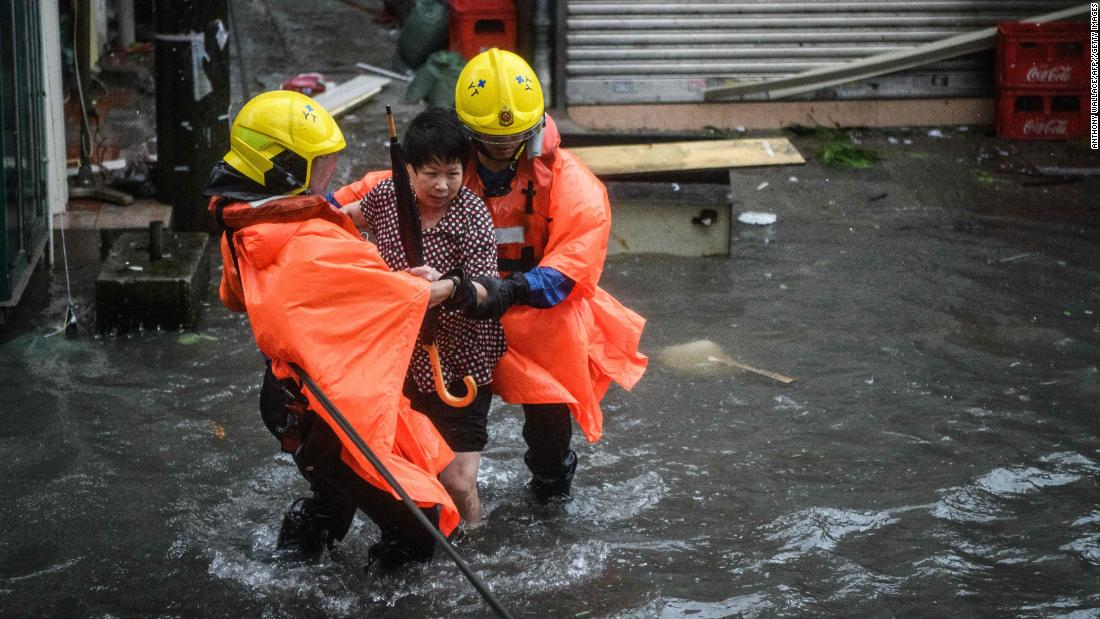 Rescue workers help a woman to cross a flooded street in the village of Lei Yu Mun, in Hong Kong on Sunday.
