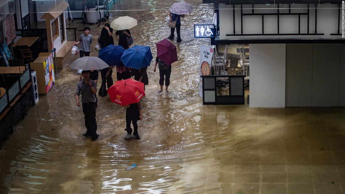 People walk through a flooded shopping mall in Heng Fa Chuen district on Sunday, September 16.