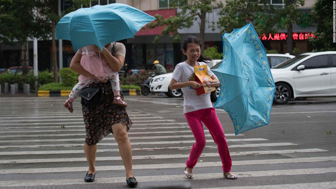 People battle strong winds as they cross a street in China's Guangdong province on Sunday, September 16.